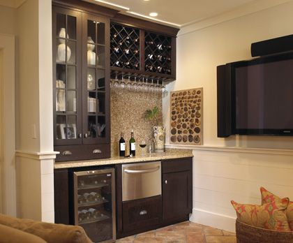 Wet bar ideas - Interesting use of space to include wine bottles and upside down storage of wine glasses.  Includes a fridge and small ice maker, but still no sink.