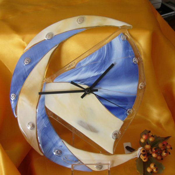 Orologio (OP01) Orologio chic da parete, che richiama il simbolo della luna. I tagli e la composizione dei vetri è particolare: i numeri sono raffigurati da spirali color argento, e le sfumature del blu opalescente e del beige brillante creano un effetto ottico molto gradevole e luminoso agli occhi di chi lo osserva.