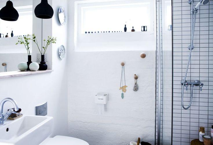 Veggene på badet er av ren, hvit mur, inne i dusjen er det derimot små fliser. Vinduet er høyt plassert på veggen, slik at dagslyset kommer inn, men man slipper innsyn. Badet har ikke et baderomsmøbel, men bare en enkel vask, og en trehylle under speilet. FOTO: Tia Borgsmidt