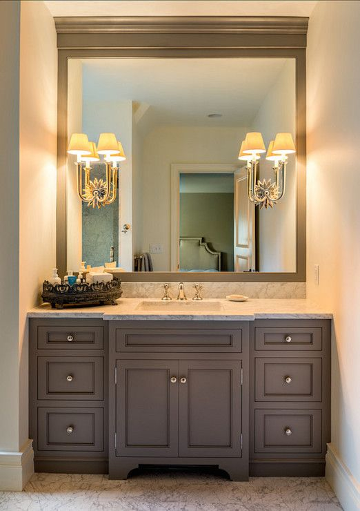 Traditional bathroom with alcove filled with gray shaker vanity accented with round nickel pulls topped with a white and grey marble counter framing a rectangular porcelain sink finished with a ceiling height mirror illuminated by sunburst wall sconces.