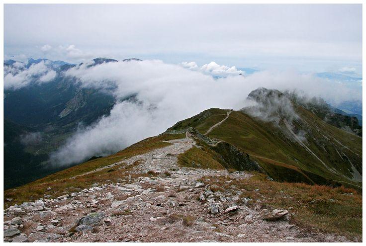 Tatry w chmurach - czerwony szlak, biegnący szczytami gór z Kasprowego Wierchu w stronę Świnickiej Przełęczy.