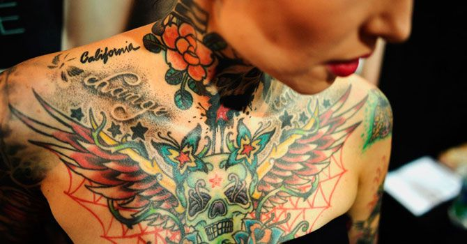 A visitor to a Tattoo and Piercing Convention event shows her tattoos in Dortmund, Germany, on June 15, 2012. —Photo (File) AP Tattoo links to HCV infection.