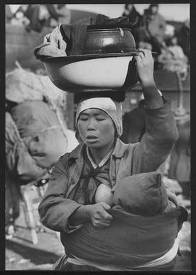 Carl Mydans: Korean mother carries her baby and worldly goods while fleeing fighting, Seoul, Korea, 1951
