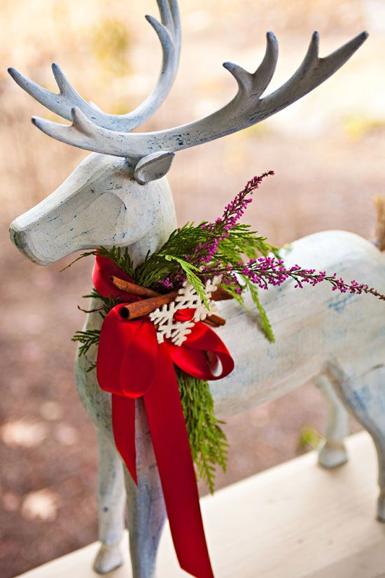 Some fresh greenery, cinnamon sticks, and a snowflake, are tied with a bright red bow to create a festive collar for a deer statue. - Traditional Home ®/ Photo: John Bessler / Design: Shazalynn Cavin-Winfrey