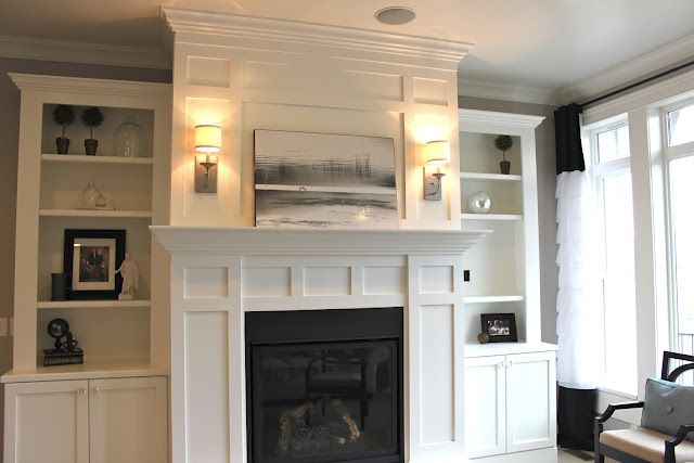 DIY fireplace & bookcases.  Love the sconces on either side of the artwork