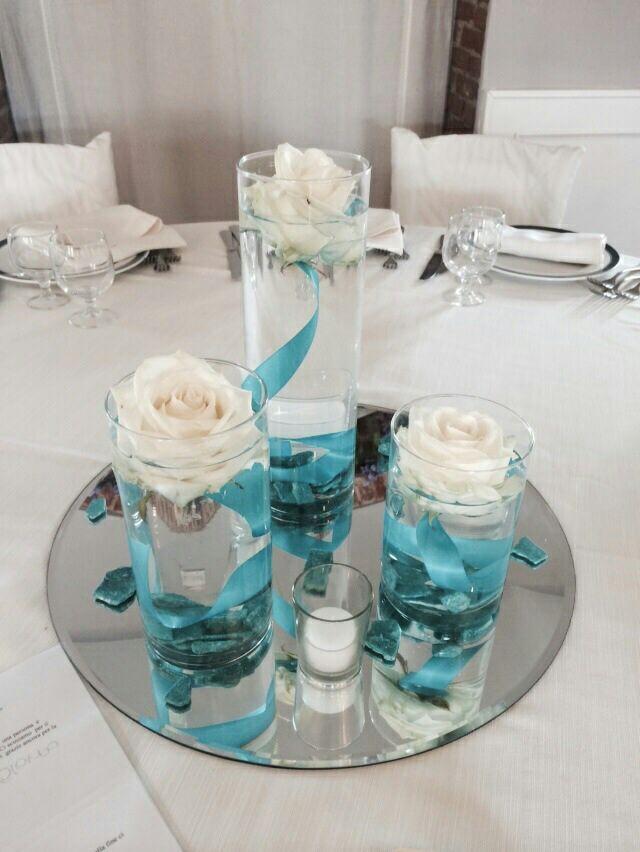 Sui tavoli una trilogia di vasi con rose bianche galleggianti, pepite tiffany, nastri ottanio e specchi illuminati da piccole candeline bianche.