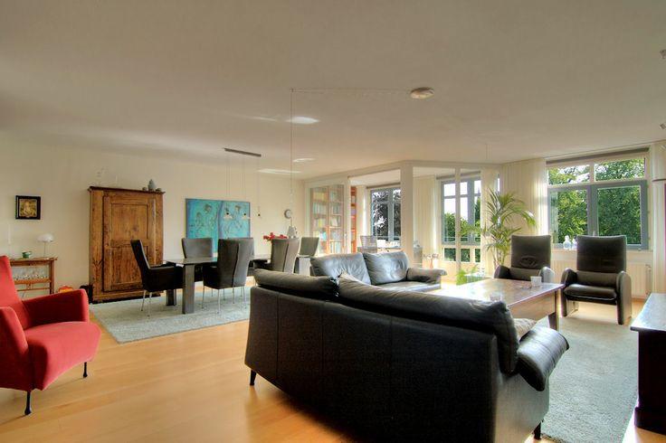 Bij binnenkomst in de royale woonkamer van circa 50m² valt direct de grootte, de hoeveelheid licht en het uitzicht op. Drie brede raampartijen zorgen voor het licht. Deze woonkamer heeft mooie lange wanden die de indeelbaarheid ten goede komen. Van de loggia zijn de deur en het raam vervangen door een schuifpui. Dit zorgt voor een prettig ruimtelijk effect en nodigt uit om de loggia intensief te gebruiken.
