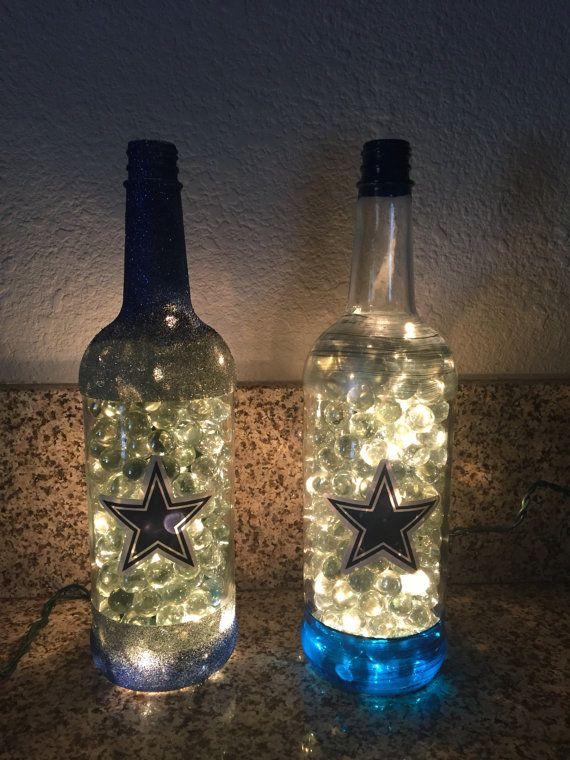 This is a 1 liter glass bottle that has been redesigned as a lighted Dallas Cowboys bottle. It has clear mini lights strung through a hole drilled in the back and has been filled with clear marbles. It has the Cowboys logo sticker on the front and blue glitter around the top and bottom. Great gift for Dallas Cowboys fans!  Other teams available upon request.