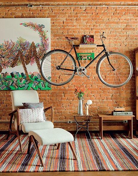 A bicicleta virou peça de decoração na sala. Ela está suspensa na parede de tijolinhos pela prateleira de madeira, da Tag