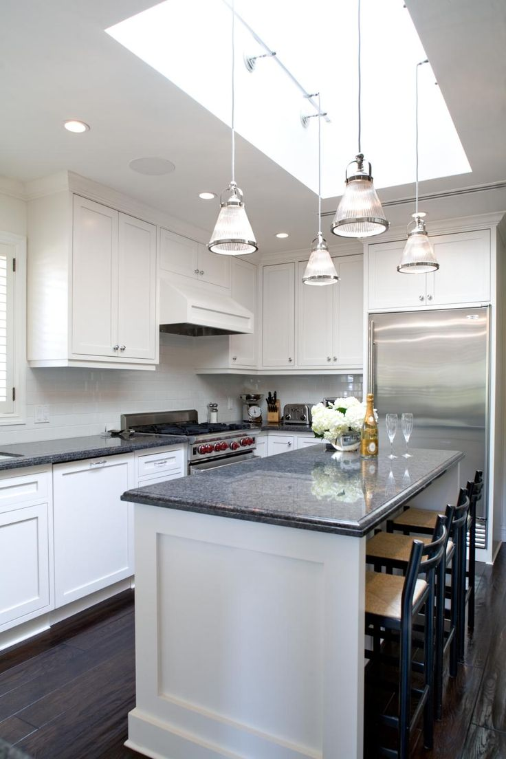 Nice This minimalistic kitchen features white cabinetry gray granite countertops and dark hardwood flooring Four