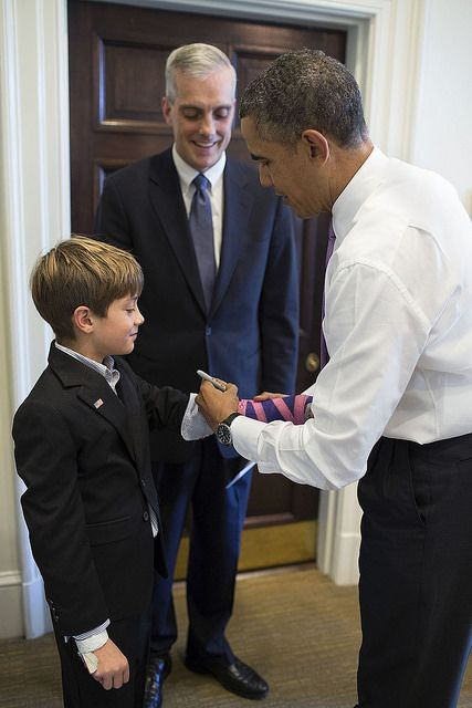 President Barack Obama signs the cast on Chief of Staff Denis McDonough's son's arm in the Outer Oval Office.
