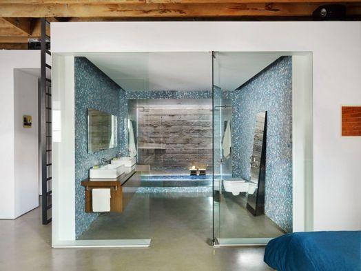 Světle modrá mozaika v kombinaci s betonem a dřevem tvoří svěží a neokoukatelný interiér koupelny..