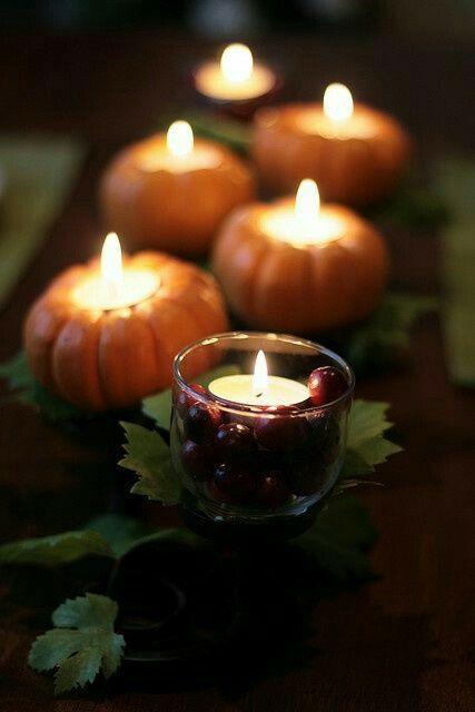 Quelques bougies incrustées dans des mini citrouilles en guise de centre de table automnal
