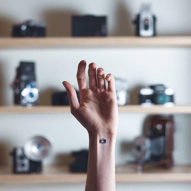 tiny camera tattoo. maybe behind the ear?