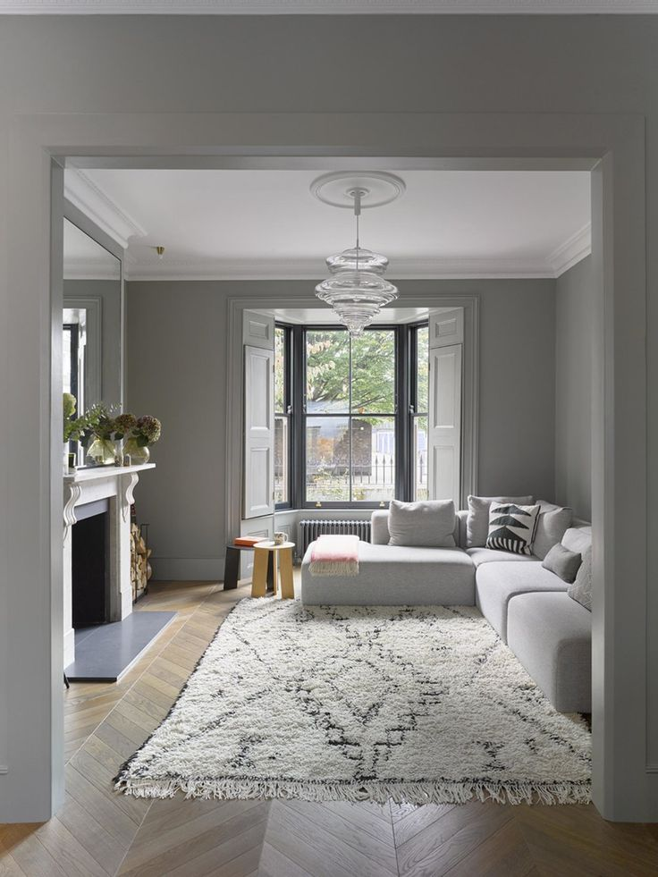 séjour gris et blanc avec parquet, moulures et cheminée + miroir. Grand canapé d'angle