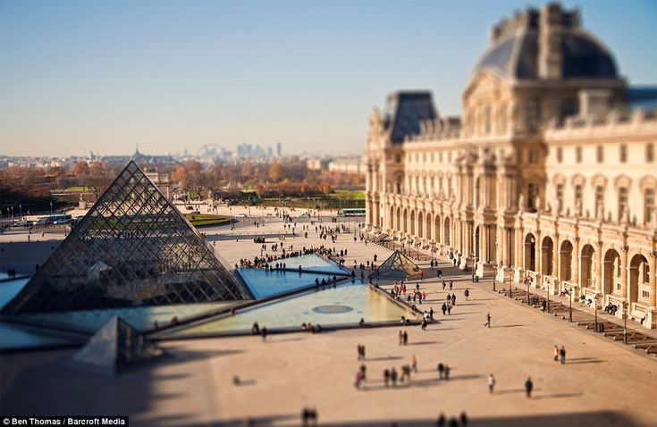THE CITY SHRINKER  Small world: Miniature people walk around the Louvre Pyramid in Paris, France in another of photographer Ben Thomas's brilliant images