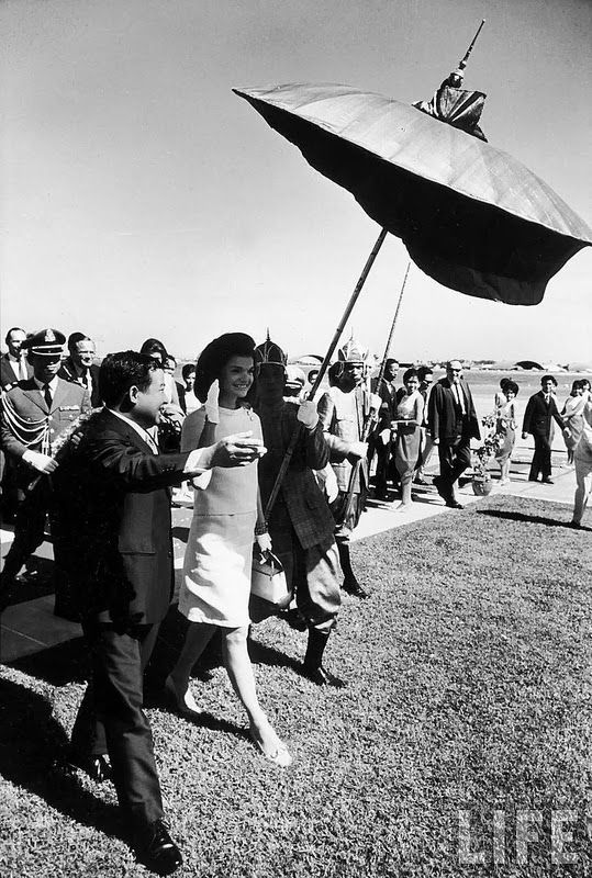 vintage everyday: Jackie Kennedy arriving in Phnom Penh and being escorted by Prince Norodom Sihanouk and the royal umbrella bearer. Nov. 1967