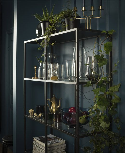A simple black shelving unit displays glass vases and other decorative items, while twine crisscrossing the side serves as a trestle for a climbing plant.