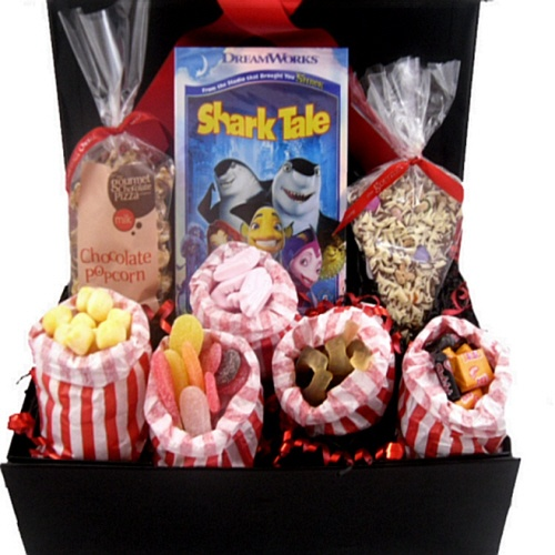 """This great """"kids movie night"""" gift box hamper comes filled with a choice of 3 kids movies and great sweet treats. Includes cola bottles, pink shrimps, sour tongues, black jacks, fruit salads and bon bon's, a fantastic slice of chocolate pizza and chocolate drizzle popcorn. Great gift on many occasions"""