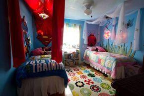 Cuarto para niño y niña decorado con telas en color rosa y rojo y con los personajes favoritos de caricaturas
