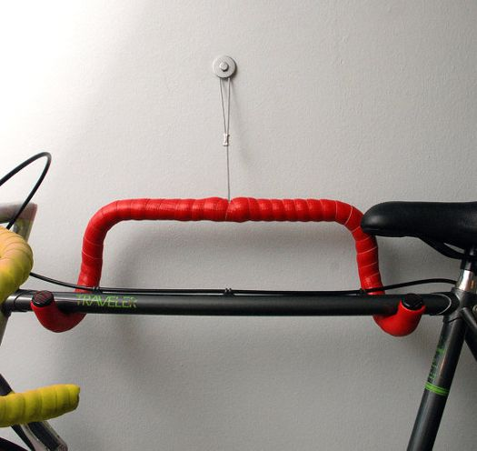 Repurposed drop handle bars into wall rack. use an old inner tube for lining if its not got strapping already.