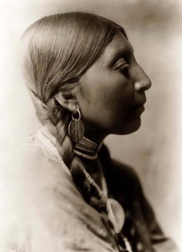 Above we show a remarkable photo of a Young Wishham Indian Woman. It was taken in 1910 by Edward S. Curtis.  The picture presents a Chinook Indian Woman in a Head-and-shoulders portrait facing right, wearing braids, shell bead choker, and abalone shell disk earrings.