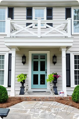 Bright turquoise storm door with light gray exterior and black shutters || Dixie Delights