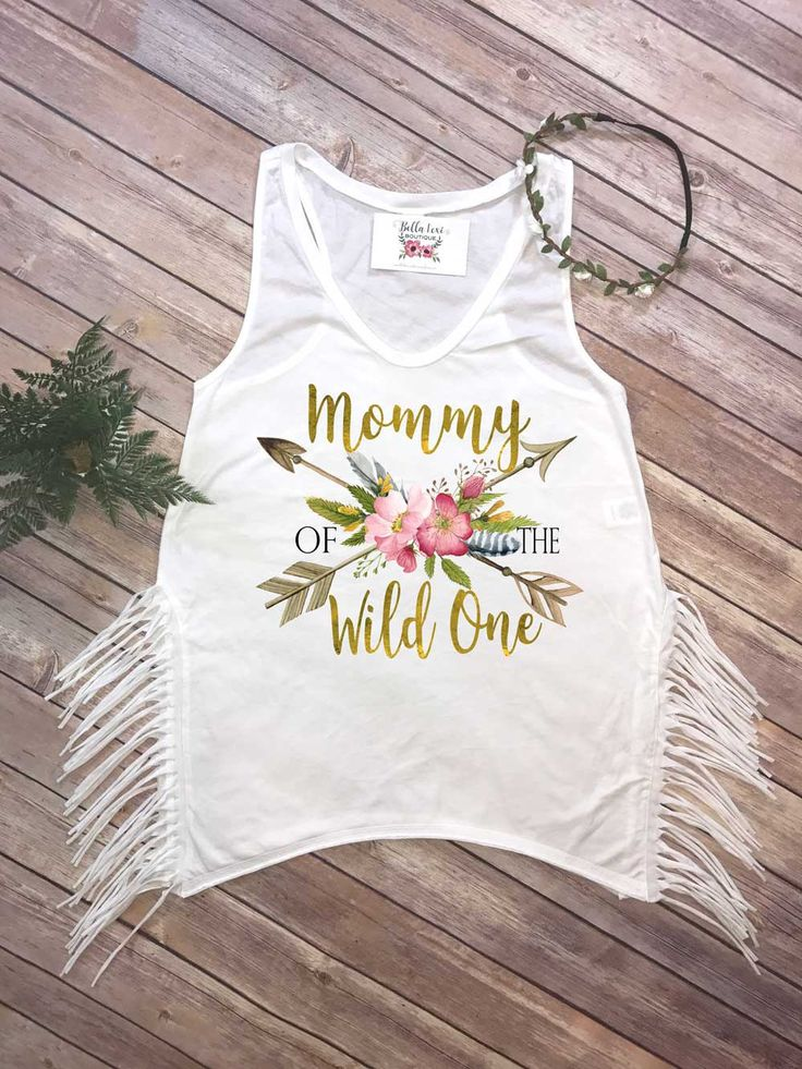 This is such an adorable Mommy of the Wild One Boho Fringe Shirt! (Available as a regular tank also!) Perfect for your little girls First Birthday Party! This design features boho style arrows and floral elements with the words Mommy of the wild one. The print has a gold look, and