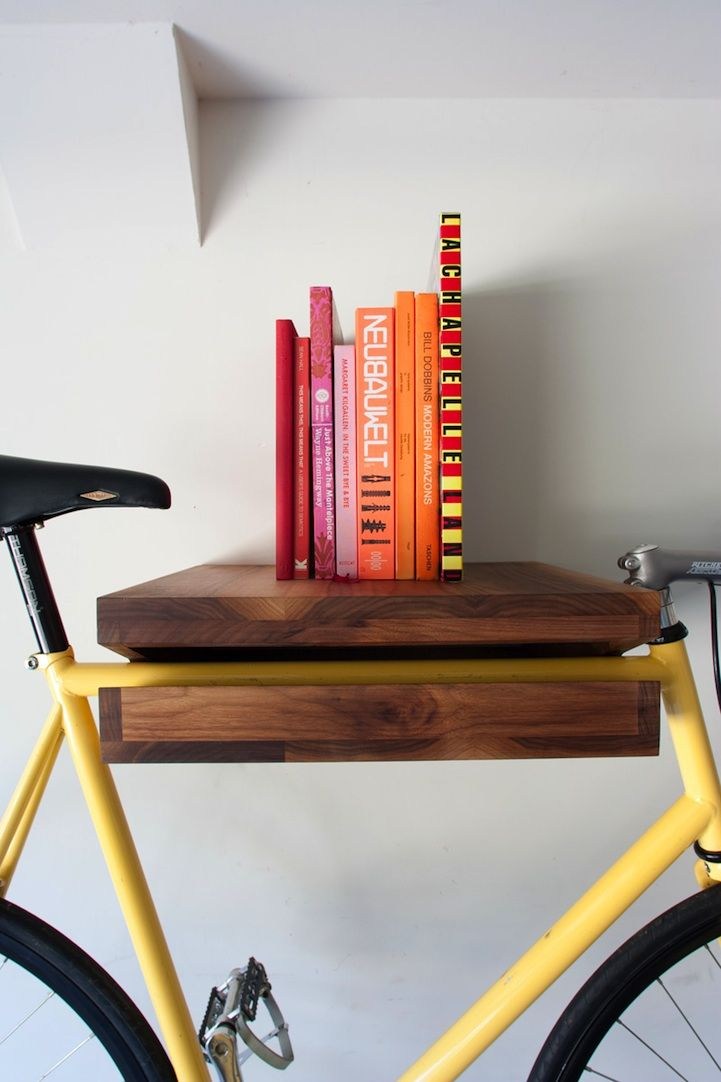 Enter the Bike Shelf. Brigham designed a beautifully crafted piece of solid wood (in this case, Walnut) and suspended it by a solid steel square rod mount. It acts as a multi-purpose shelf, able to gracefully display your books