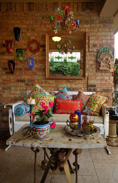 Eclectic. ~~~Love the table base. Nice collection of pillows. I do not like the rest of this room. Needs rug, wall arrangement too high, mirror should be hung horizontally, lower chandelier a bit. Más                                                                                                                                                                                 Más