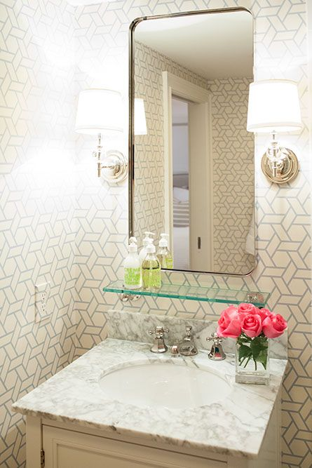 Chic powder room features white and gray trellis wallpaper, Manuel Canovas Trellis Wallpaper, framing a small washstand cabinet topped with gray marble countertop framing oval sink and vintage style faucet kit under vintage glass shelf under curved vanity mirror illuminated by Robert Abbey The Muses Calliope 1 Light Wall Sconces.