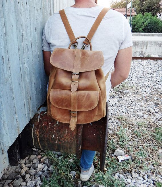 This classic unisex medium size backpack/rucksack is handmade with Greek full grain cowhide leather in its light brown color and has no lining. It features a main section that closes with a drawstring closure and a fold-over flap with a metal buckled strap. With an additional pocket on the front zipped pocket on the back, for quick access, this fair sized rugged and yet elegant bag is adorned with stitched detail.  DIMENSIONS:  Height: 12.99 / 33 cm Width: 11.42 / 29 cm Depth: 5.5 / 14 cm…
