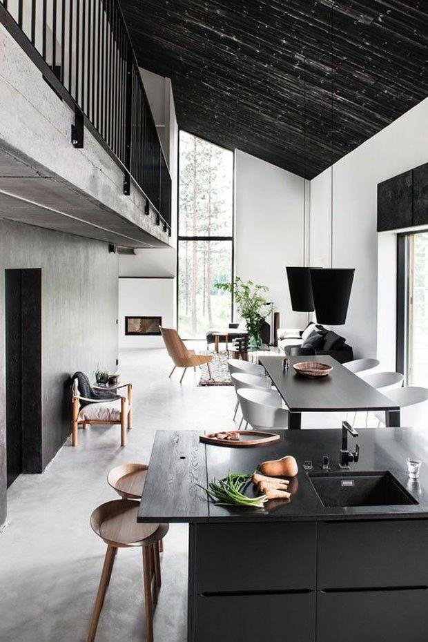 Integradas, as salas de estar, jantar e cozinha se mantém clássicas, com o décor todo em preto e branco -- quebrado apenas pelos tons de madeira clara nas banquetas, cadeiras e poltronas. Esta combinação, inclusive, evoca o estilo escandinavo desta casa na Finlândia.