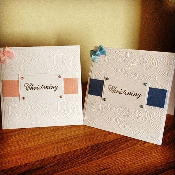 "Classical Handmade Christening Cards  These cards are made in a simple but elegant style to welcome in a new generation!  The cards are 5″ x 5″ and layered using high quality white cardstock, with the main feature being a pretty, embossed panel.  There are two variations, one with blue embellishments (ribbon, gems and bow) for a boy and one with pink embellishments for a girl.  Sitting on top of the wide ribbon is simply the word ""Christening"", stamped in an elegant typeface."