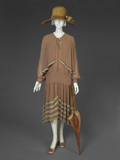 """Dress, Lucien Lelong (French, 1889 - 1952): ca. 1926, silk crepe-de-chine, silk looped fringe. """"...Lelong introduced in 1925 the concept of """"kinetic design""""-practical clothing for the modern woman that stressed freedom of movement. The principle is embodied in this afternoon dress with its full paneled skirt, lowered waistline, and decorative fringe, which swings as the wearer moves. Lelong was very popular with American women..."""""""