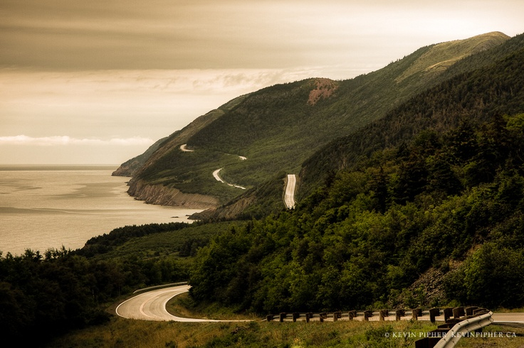 """A narrow road winds through the rugged coastline and untouched wilderness. Cape Breton Highlands, Nova Scotia."""