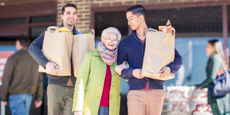 Dos hermanos jóvenes ayudan a una hermana mayor con las bolsas del supermercado