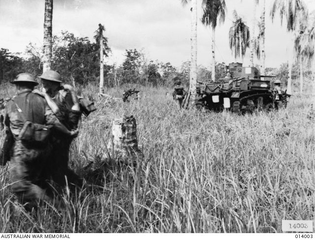 1943-01-02. PAPUA, GIROPA POINT. GENERAL STUART M3 TANKS MANNED BY 7 TROOP, B SQUADRON, 2/6TH ARMOURED REGIMENT, ATTACK JAPANESE PILLBOXES IN THE FINAL ASSAULT ON BUNA. ON THE LEFT, WOUNDED SOLDIER ...