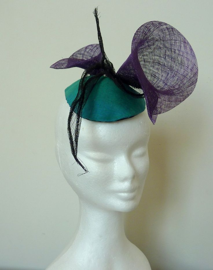 Melbourne cup hat purple/cocktail hat teal Teal silk kidney shaped hand-blocked base. Large purple sinamay trumpet flowers and black sinamay sprigs.
