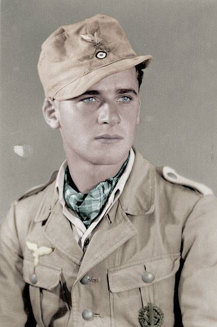 Fine studio pose by a young Luftwaffe private in a pale tan tropical uniform, serving with the Afrika Korps. The breast eagle is machine-embroidered in grey cotton on a tan twill base. Collar patches were not worn on the tropical tunic. He proudly displays his SA Sports Badge.