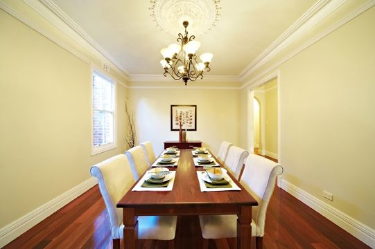 Classic style dining room with high ceiling, feature cornice, ceiling rose and beautifully polished jarrah floorboards.