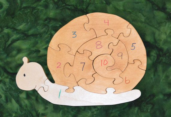 """This Snail Puzzle is here to help your child learn to count to 10, as it spirals into the center. Puzzles help to develop small motor, hand-eye coordination, visualization and problem solving skills all of which are important in the process of reading. Dimensions: 7.75"""" high, 11"""" long"""