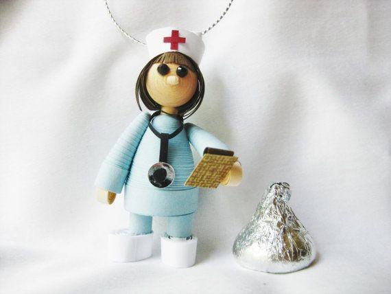 Cette adorable infirmière peu dresse juste 2 1/2(6 cm) hauteur du bas de ses chaussures pratiques à la pointe du chapeau de ses infirmières traditionnel. Fabriqué à partir de papier, elle porte bleus ciel scrubs, un stéthoscope de papier minuscules autour de son cou et porte un presse-papiers avec graphique. Elle est unique et adorable !  Cette petite infirmière serait faire un cadeau de décoration ou de l'obtention du diplôme de grand arbre de Noël pour l'infirmière dans votre vie. Vous…