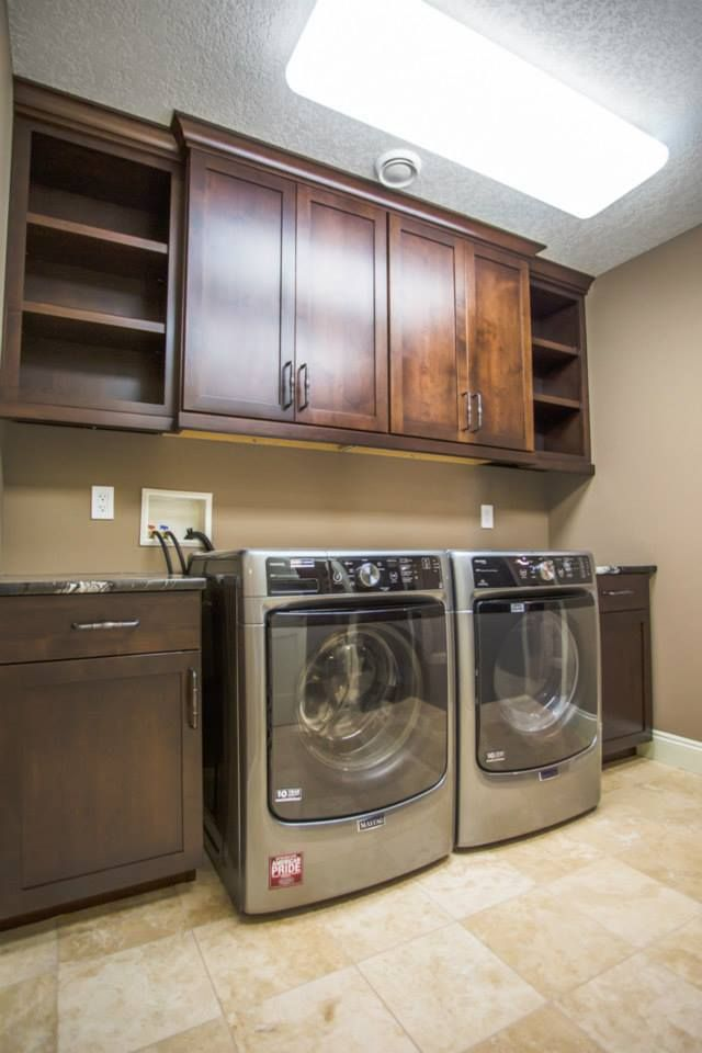 Side by side washer and dryer built in with counter on each side and cabinets over head for added storage