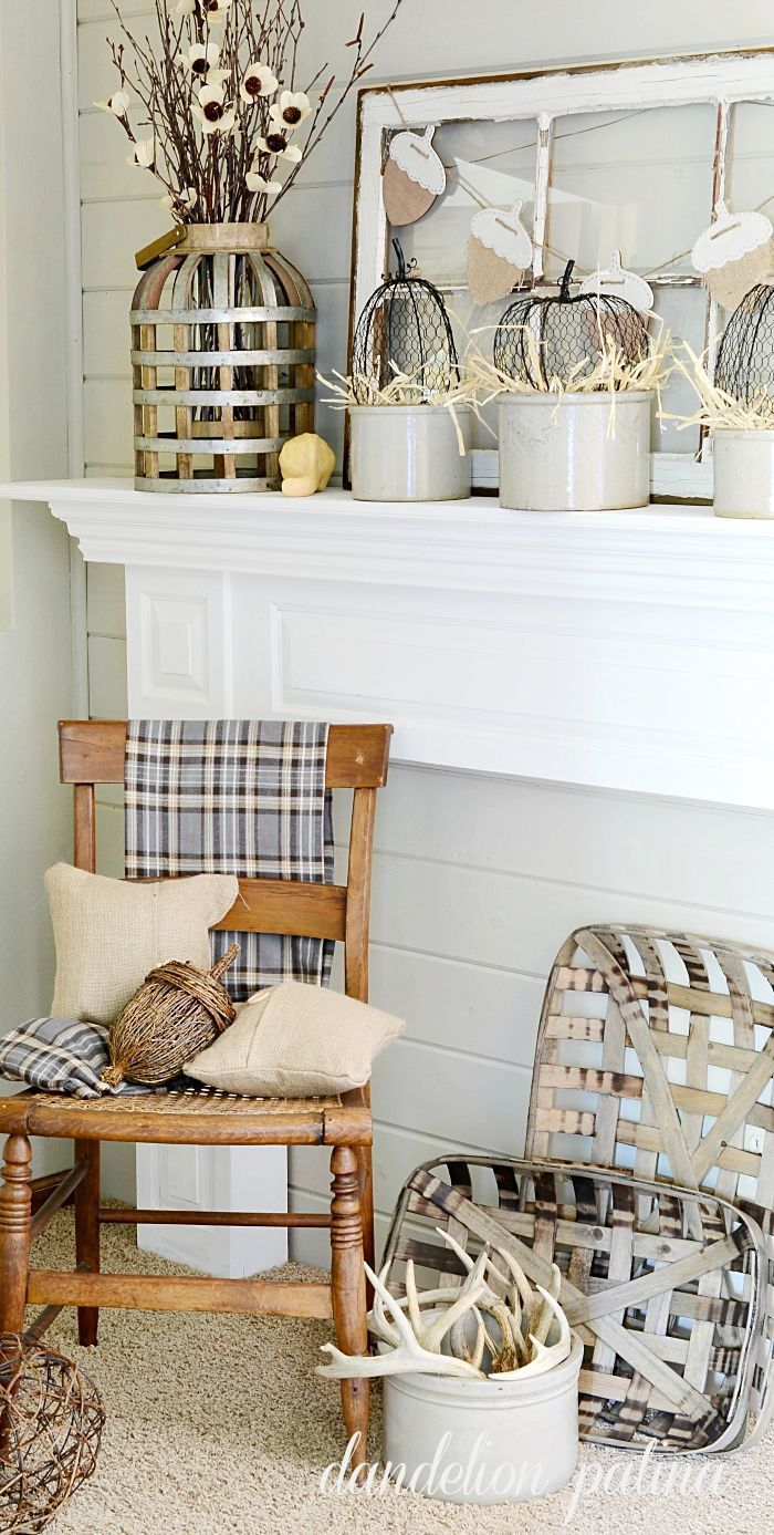 Neutral fall mantel incorporating farmhouse style with vintage wooden chair, tobacco baskets, and burlap pillows.