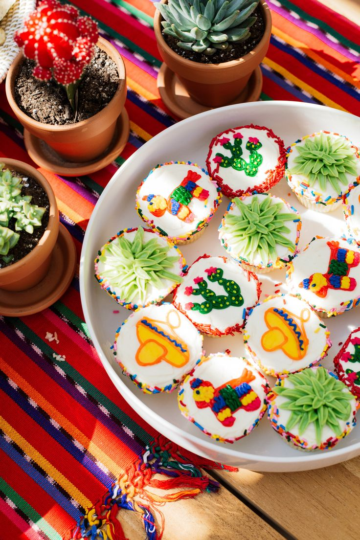 Fiesta Cupcakes // Throwing a Fiesta style party? Order cupcakes with sombreros, piñatas, cacti, and succulents to complete your Mexican style theme // http://www.eatsleepwear.com/2016/09/21/lolas-fiesta/