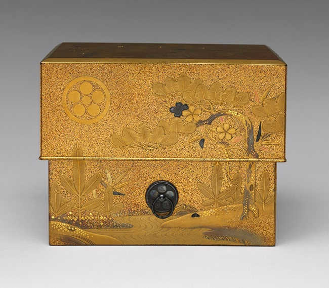 Incense box (jinbako), Edo period (1615–1868), ca. 1830  Japan  Maki-e decorated lacquer; on pear-skin (nashiji) background pine, bamboo, and cherry blossoms, and the Shimazu and Matsudaira family crests. This box for storing incense wood includes an inner tray and six small incense containers as well as wrapping papers for the aloe incense wood. The small boxes are decorated with patterns referring to chapters of the Tale of Genji.
