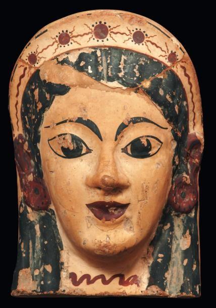 Néolithique & Antiquité classique : Antéfixe à visage féminin. Il représente une koré souriant, les yeux allongés, légèrement obliques, surmontés de fins sourcils courbes. Vendu aux #encheres le 01/12/11 par Pierre Bergé & associés