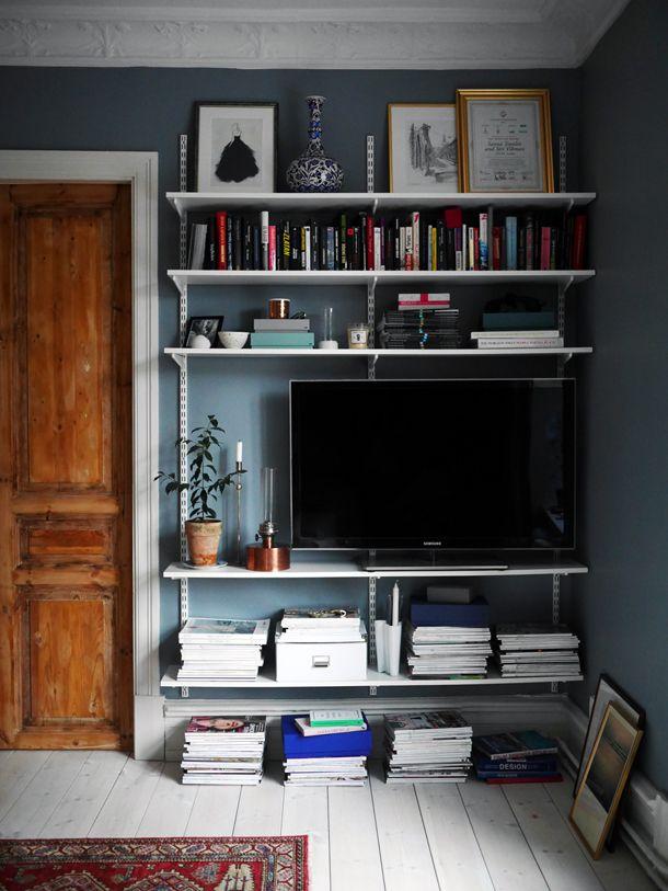 Light blue wall, white floorboards and a white bookshelf // Weißes Bücherregal, weiße Holzdielen und mittelblaue Wand mit weißem Stuck