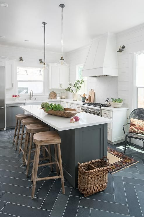 Four wood tractor seat counter stools sit on gray slate herringbone at a dark gray center island contrasted with a white quartz countertop lit by clear glass lanterns.